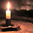 Burning candle in an old wine cask in the wine cel...