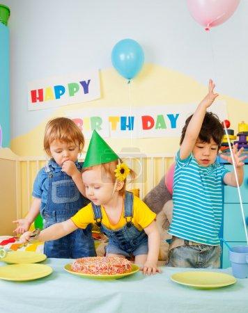 Photo pour Trois enfants s'amusant sur la fête d'anniversaire - deux garçons et une fille - image libre de droit