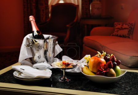 Photo for Romantic evening with bottle of champagne, sweets and fruits in the hotel room - Royalty Free Image