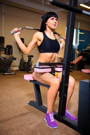 Attractive young woman doing exercises at the gym