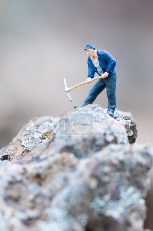 Figure of miner with pickaxe at work....