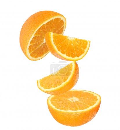 Fresh orange slices in motion over white
