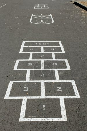 Photo for A few hopscotch game courses are outlined on the pavement of a children's playground on a sunny morning. - Royalty Free Image