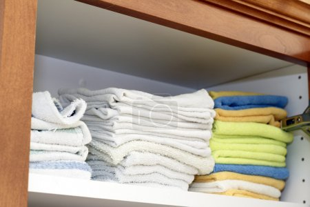 Photo pour Une variété de chiffons de nettoyage pliés sur une étagère dans une armoire de cuisine . - image libre de droit