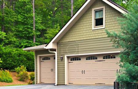 Photo for Garage doors on a modern house. Double doors with windows on one side and an off-set single beside it. - Royalty Free Image