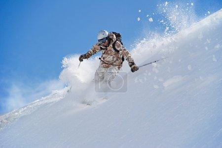 Photo pour Skieur dans la neige profonde. à son tour déclenche la poussière de neige. sur le fond du ciel - image libre de droit
