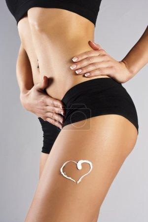 Woman applying moisturizer cream on legs. Perfect female figure