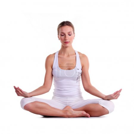 Photo for Young woman practicing yoga, sitting in a lotus position - Royalty Free Image