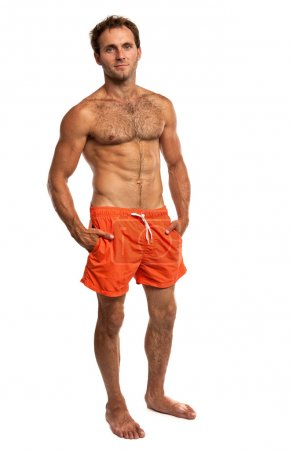 Muscular young man in swimwear standing on white