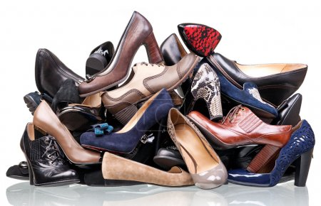 Pile of various female shoes isolated over white