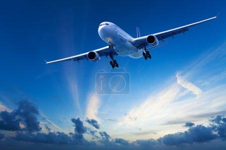 Photo pour Vol en soirée : avion à réaction en croisière dans un ciel bleu après le coucher du soleil - image libre de droit