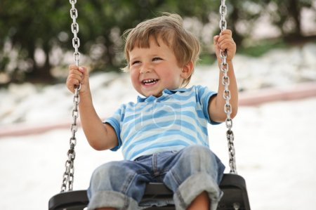Photo for Little boy having fun on chain swing - Royalty Free Image