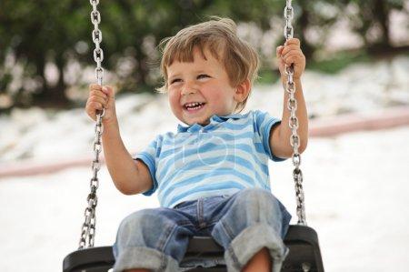 Foto de Niño divirtiéndose en columpio de cadena - Imagen libre de derechos