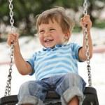Little boy having fun on chain swing...