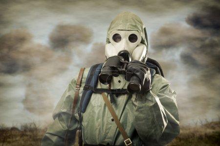 Man in gas mask with binocular