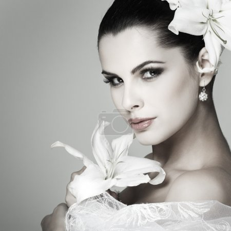 Elegant sexual brunette in a wedding-dress with lilies in hairs
