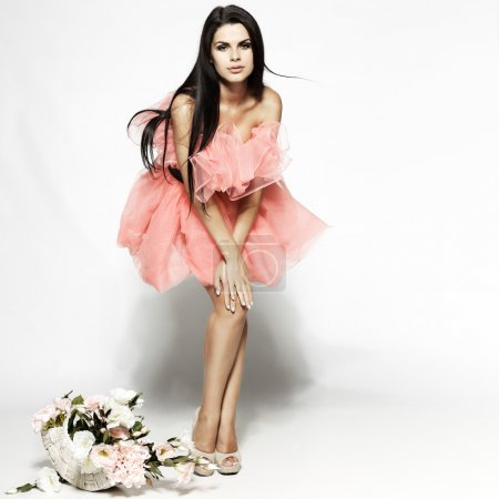 Photo for Beautiful sexual brunette in pink clothes with the basket of flowers - Royalty Free Image