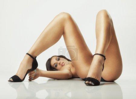 Photo pour Fille de pose sexy glamour gisant sur le sol blanc - image libre de droit