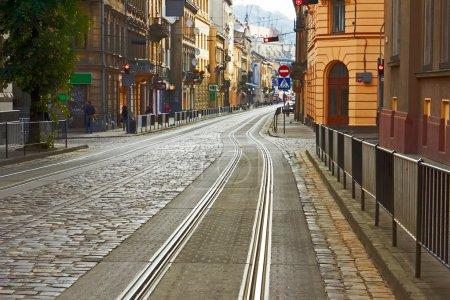 Photo pour Ancienne route pavée avec des voies de tram dans le centre-ville dans la matinée à lviv, ukraine - image libre de droit
