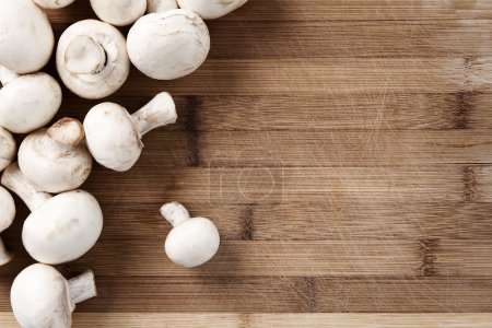 Photo for Fresh champignons at the old cutting board with copy space - Royalty Free Image