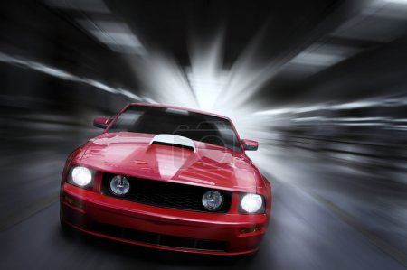 Photo for Luxury red sport car speeding in a underground parking garage - Royalty Free Image