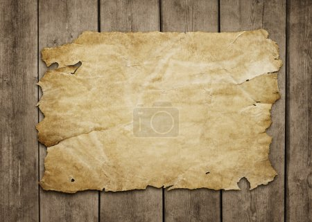 Old paper at grunge wooden background