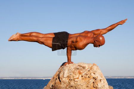 Photo for Balance strong man balancing on rock. - Royalty Free Image