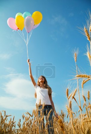 Teen girl at a wheat field with balloons