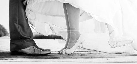 Photo pour Jambes de la mariée et le marié, debout sur un pont - image libre de droit