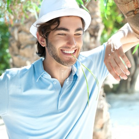 Young man wearing hat and casual clothes in sunny day. Leaning o