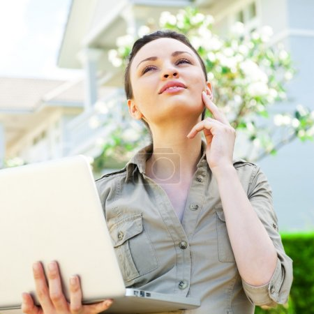 Young pretty female realty agent with laptop presenting beautifu