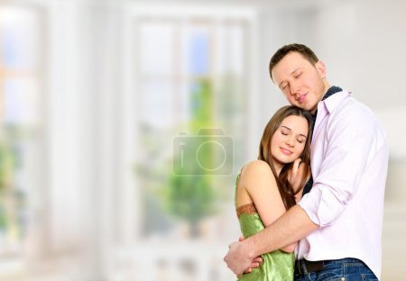 Cosy young couple embracing inside new apartment and planning to