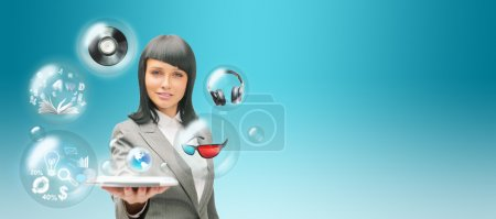Photo for Pretty business woman holding tablet computer and different objects are flying from touch screen - Royalty Free Image