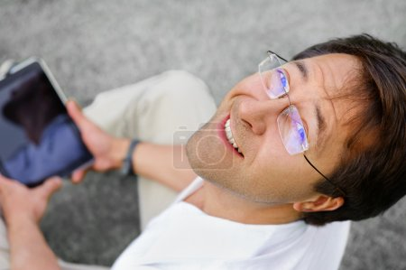 Handsome relaxed and positive man is surfing on his tablet