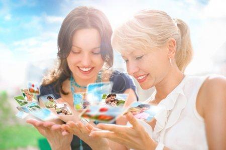 Foto de Retrato de dos mujeres feliz madre e hija mirando sus archivos de foto y video en medios sociales mediante interfaz virtual del futuro. al aire libre en el hermoso lugar idílico. - Imagen libre de derechos