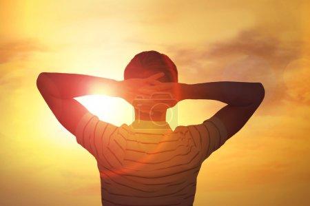 Photo pour Homme adulte satisfait de la beauté de la nature du coucher du soleil. Photo de derrière contre le soleil - image libre de droit