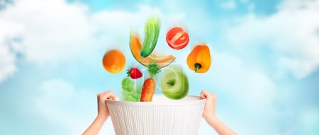 Hands are holding basket against sky background, vegetables, fruits and berries are falling into this basket