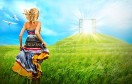 Young woman running across beautiful field to the bright luminous door on a hill