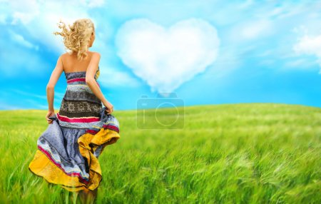 Portrait of romantic woman running across field to her love