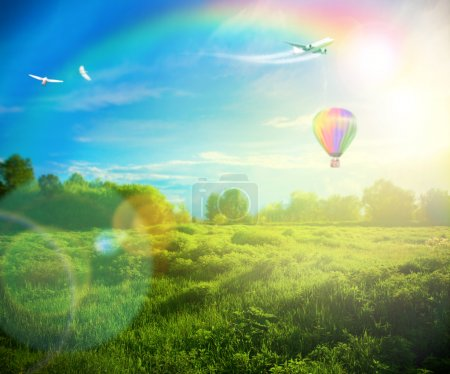 Photo for Beautiful image of stunning sunset with atmospheric clouds and sky over vibrant fields in countryside landscape with hot air balloon, birds and airplane flying high - Royalty Free Image