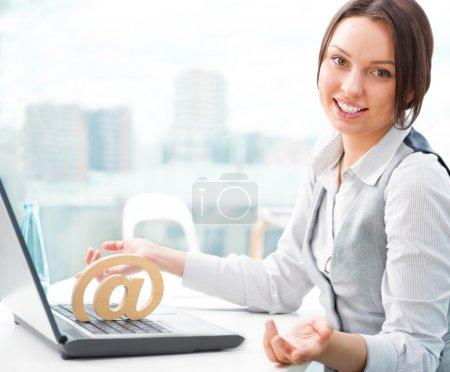 Photo pour Portrait d'une femme d'affaires gai assis sur son bureau et souriant. arobas sur son portable - image libre de droit