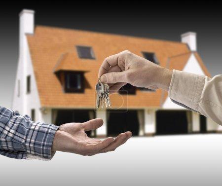 Photo pour L'homme est remise une clé de la maison d'un autre homme en forme de la maison. - image libre de droit