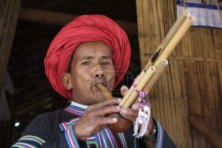 Thailand, Chiang Mai, Karen Long Neck hill tribe village (Kayan Lahwi), Karen man in traditional costumes playing a flute