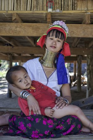 Thailand, Chang Mai, Karen Long Neck hill tribe village (Kayan Lahwi), Long Neck child and his mother in traditional costumes. Women put brass rings on their neck when they are 5 or 6 years old and in
