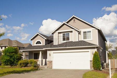 Photo pour Nouvelle belle maison de banlieue avec ciel bleu et nuages - image libre de droit