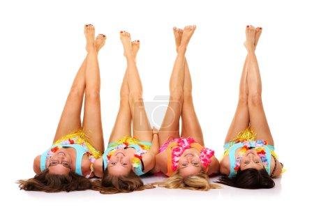 Photo pour Une photo de quatre copines allongées sur le sol dans des jupes hawaïennes avec leurs jambes vers le haut sur fond blanc - image libre de droit