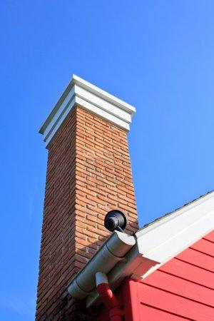 Orange brick pipe and black roof on blue sky