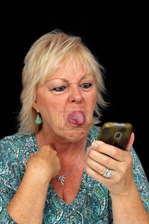 Photo pour Un gros plan d'une jolie femme blonde plus âgée qui est en colère par quelque chose sur son téléphone cellulaire et qui sort sa langue dessus . - image libre de droit