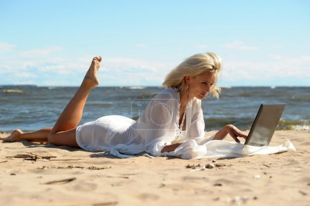 Happy blonde woman at a beach with a laptop