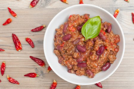 Photo for Chilli Con Carne in White Bowl and Chili Peppers - Royalty Free Image
